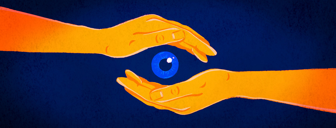 Two cupped hands form the shape of an eye around a floating iris and pupil.