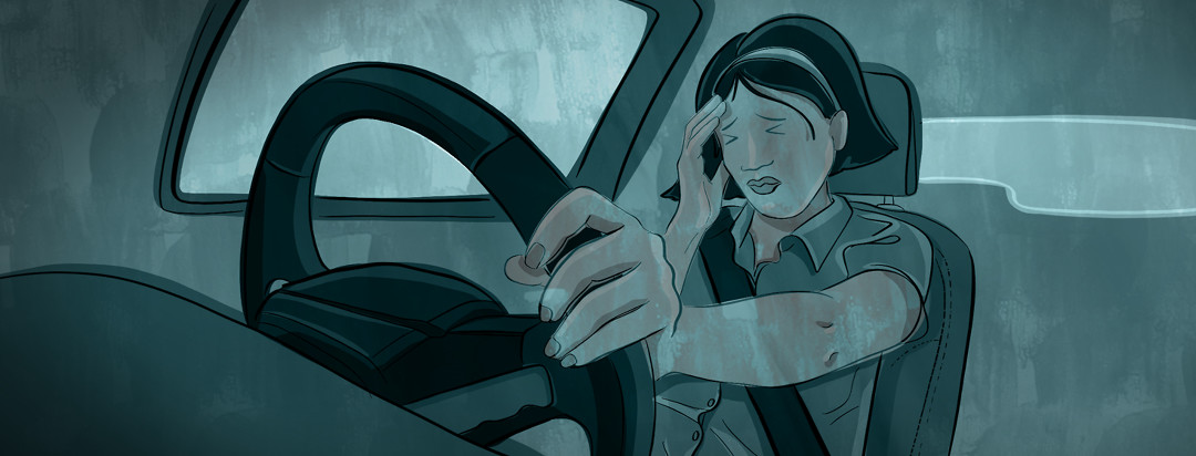 A woman behind the steering wheel of a car clutches her head and winces her eyes.