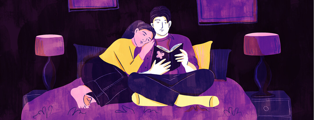 A couple cuddles together on a bed and both read from a book with a butterfly on it.