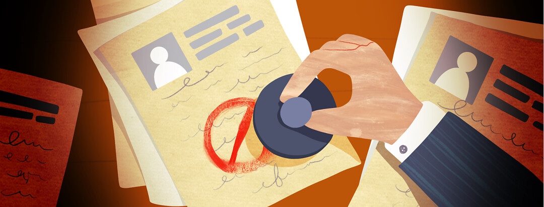 A hand stamps a red crossed out circle over top of a document on a table.