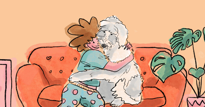 A woman sits on a couch and hugs her white fluffy dog.